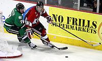 UNO's Eric Olimb brings the puck from behind the UNO net while being defended by North Dakota's Danny Kristo. No. 4 UNO beat No. 7 North Dakota 1-0 Saturday night at Qwest Center Omaha. (Photo by Michelle Bishop)