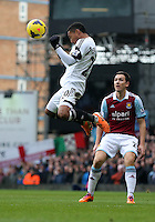 Pictured L-R: Jonathan de Guzman of Swansea heads the ball away, against Stewart Downing of West Ham looks on. 01 February 2014<br />
