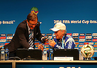 Argentina coach Alejandro Sabella gets help from a FIFA official for his broken headset during the press conference
