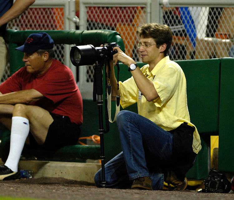 "Tom Williams staff photographer for Roll Call Photos ""chimps"" photos on his digital camera during the 45th Annual Roll Call Congressional Baseball Game at RFK Stadium in Washington D.C."