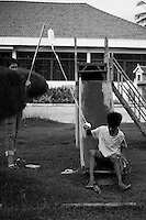 Young boy on a drip playing in the hospital yard.