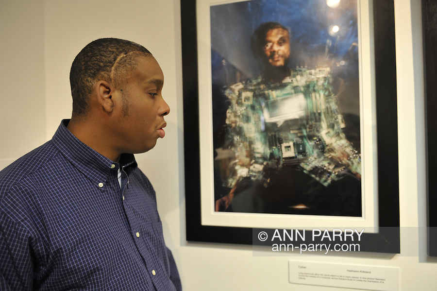 """Hasheem Kirkland, a vision impaired photographer, facing his """"Cyborg"""" photograph, at Artist Reception for Seeing with Photography Collective SWPC, a group of visually impaired, sighted and totally blind photographers based in NYC, on Saturday, April 28, 2012, at African American Museum, Hempstead, New York, USA, and hosted by Long Island Center of Photography. Aperture published the group's """"Shooting Blind: Photographs by the Visually Impaired"""" in 2005."""