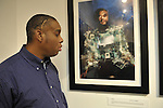 "Hasheem Kirkland, a vision impaired photographer, facing his ""Cyborg"" photograph, at Artist Reception for Seeing with Photography Collective SWPC, a group of visually impaired, sighted and totally blind photographers based in NYC, on Saturday, April 28, 2012, at African American Museum, Hempstead, New York, USA, and hosted by Long Island Center of Photography. Aperture published the group's ""Shooting Blind: Photographs by the Visually Impaired"" in 2005."