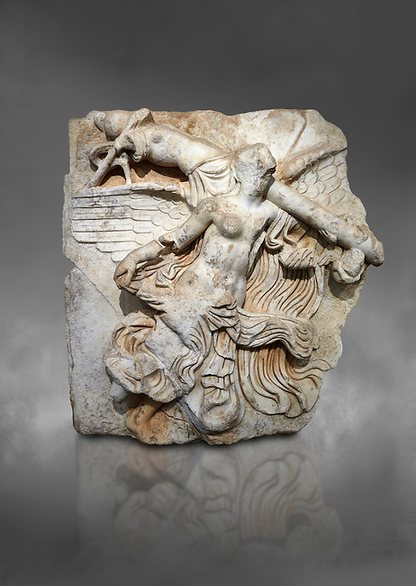 """Roman Sebasteion relief  sculpture of Victory of the Emperors, Aphrodisias Museum, Aphrodisias, Turkey.  Against a grey background.<br /> <br /> The inscription identifies the subject of the relief panel as the """"Victory of the Emperors"""" (Neike Sebaston), and refers to the conquest of Armenia and Britannica in its adjacent relief panels. A half naked Victory flies diagonally across the panel, carrying a military trophy over her shoulder. A small winged Eros, now damaged was clinging to the end of the trophy pole. Victory was a key imperial attribute"""