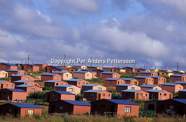 SOWETO, SOUTH AFRICA - FEBRUARY 19: Hundreds of colorful newly built RDP (rapid development program) government sponsored houses, also known as Mandela houses, on February 19, 2004 side by side in Soweto outside Johannesburg, South Africa. The government promised to build one million houses during the election in 1994 and about 1,7 million houses have been built. Still the housing backlog are estimated to about 6-7 million units, making it still a dream for many poor people in South Africa to own a house. .Photo: Per-Anders Pettersson/ iAfrika Photos....