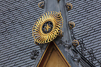 Sculptural detail of a star within a sun with curved rays of gilded lead, symbol of charity, on a Gothic weathervane in the courtyard of Les Hospices de Beaune, or Hotel-Dieu de Beaune, a charitable almshouse and hospital for the poor, built 1443-57 by Flemish architect Jacques Wiscrer, and founded by Nicolas Rolin, chancellor of Burgundy, and his wife Guigone de Salins, in Beaune, Cote d'Or, Burgundy, France. The buildings, set around an internal courtyard, are in Northern Renaissance and Flamboyant Gothic style, with half-timber galleries, ornate rooftops with Burgundian glazed tiles in geometric patterns and dormer windows. The hospital was run by the nuns of the order of Les Soeurs Hospitalieres de Beaune, and remained a hospital until the 1970s. The building now houses the Musee de l'Histoire de la Medecine, or Museum of the History of Medicine, and is listed as a historic monument. Picture by Manuel Cohen