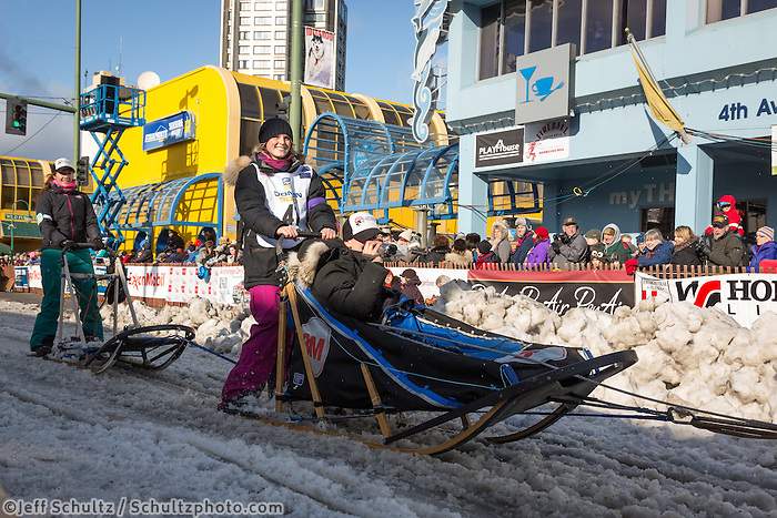 Lisbet Norris and team leave the ceremonial start line with an Iditarider at 4th Avenue and D street in downtown Anchorage, Alaska during the 2015 Iditarod race. Photo by Jim Kohl/IditarodPhotos.com