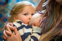 Close-up of a child of about 29 months breastfeeding while looking at the camera.