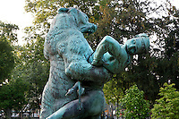 Mid-length view of the statue called Le Denicheur d'ourson (The Bear Cub Thief) created by Emmanuel Fremiet in 1884 and cast by Thiebaut Freres, located in the Jardin des Plantes, Paris, 5th arrondissement, France. Founded in 1626 by Guy de La Brosse, Louis XIII's physician, the Jardin des Plantes, originally known as the Jardin du Roi, opened to the public in 1640. It became the Museum National d'Histoire Naturelle in 1793 during the French Revolution. Picture by Manuel Cohen