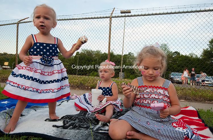 NAUGATUCK, CT-070614JS11--Sisters Madalynn Warzecha, 19-months, Abagail Warzecha, 19-months and Maci  Warzecha, 3, enjoy ice cream while waiting for the fireworks to begin  during the annual Naugatuck 4th of July Celebration Sunday in Naugatuck. <br /> Jim Shannon Republican-American
