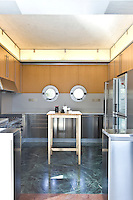 The functional stainless steel kitchen has a dark green marble floor and features a pair of porthole windows
