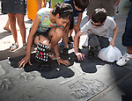 A brother and sister put their hands into the hand prints of actors from Harry Potter in the Forecourt of the Stars at Grauman's Chinese Theatre, Hollywood, Los Angeles, CA