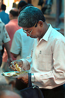 A Office worker having lunch during break at  a street food stall in Dalhousie area of Kolkata. Street food stalls are serving the office goers for decades. All kind of Indian foods are available on the street at an affordable price. They sale them openly. Street food stalls are another results of unempoloyment and over poppulation. They serve millions of people in India. Kolkata, West Bengal,  India  7/18/2007.  Arindam Mukherjee/Landov
