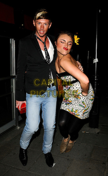 "LOIS WINSTONE & GUEST.Perfume launch of her new fragrance ""Controversial"", Embassy Club, London, England..July 29th, 2008.full length black dress white pattern floral print strapless yellow flower in hair hand in pocket leggings brown shoes jacket tie jeans denim hat funny posing bending leaning puckering lips .CAP/CAN.©Can Nguyen/Capital Pictures."