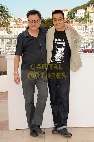 Director Eric Khoo (L) and actor Yoshihiro Tatsumi attend the 'Tatsumi'  photocall at the Palais des Festival, 64th International Cannes Film Festival, France.17th May 2011.full length jeans denim black grey gray beige jacket top glasses arm over shoulder .CAP/PL.©Phil Loftus/Capital Pictures.
