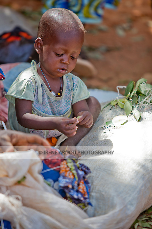In the town of Djibo in northern Burkina Faso, a child plays quietly as her mother sells greens in the market.