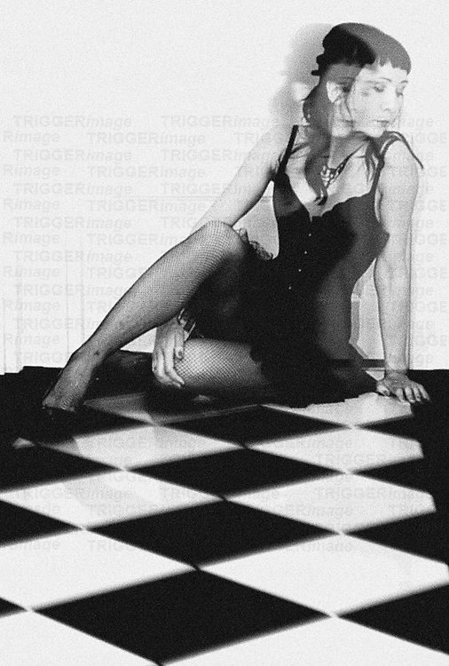 A young woman dressed inblack pin up dress with corset sitting on the black nad white floor looking down