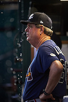 Mississippi Braves pitching coach Dennis Lewallyn (50) watches from the dugout as it rains during a game against the Mobile BayBears on April 28, 2015 at Hank Aaron Stadium in Mobile, Alabama.  The game was suspended after the top of the second inning with Mobile leading 3-0, the BayBears went on to defeat the Braves 6-1 the following day.  (Mike Janes/Four Seam Images)