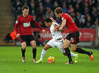 Craig Dawson of West Bromwich Albion (R) challenges Jefferson Montero of Swansea (C) during the Barclays Premier League match between Swansea City and West Bromwich Albion played at the Liberty Stadium, Swansea on December 26 2015