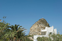 The simple white holiday home with its large covered terrace seen against the backdrop of a large outcrop of rock and a clear blue sky