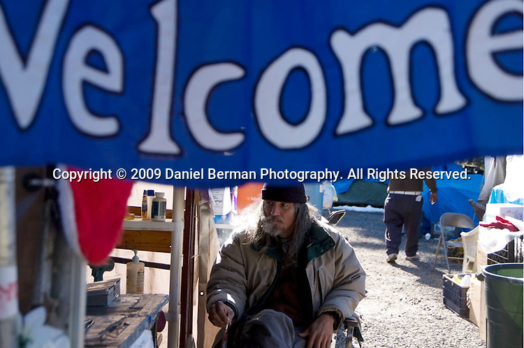 Resident Mark Ackerman smokes a cigarette at the entrance to Tent City 3 at Calvin Presbyterian Church February 27, 2009 in Shoreline, WA. After three months in Shoreline, Tent City 3 will be making a new home at Saint Mark's Cathedral near downtown Seattle.