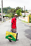 "JAMAICA, Port Antonio. Derrick ""Johnny"" Henry of the Mento band, The Jolly Boys, carrying the marumba box."