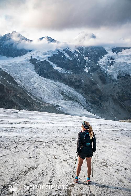 A woman trail runner stands on a glacier beneath the alpine peaks above Zermatt, Switzerland.