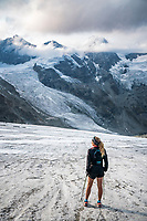 A woman trail runner stands on a glacier beneath the alpine peaks above Zermatt, Switzerland.