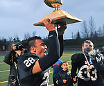 Drew Gibbs brings the trophy to his teammmates.  Photo for the Clarion by Michael Dinneen