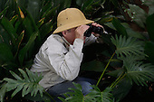 Stock photo of Bird watcher and explorer looking through binoculars