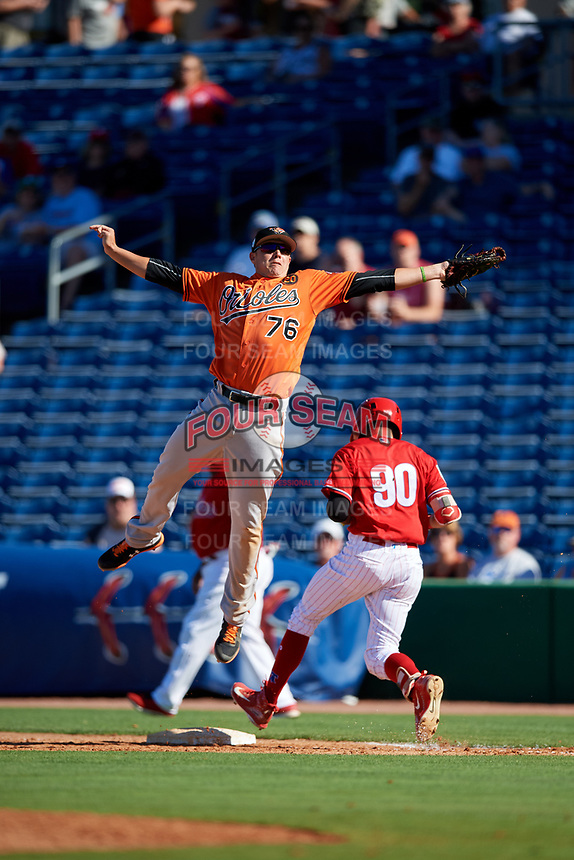 Baltimore Orioles first baseman Ryan Mountcastle (76) jumps to catch an errant throw as Simon Muzziotti (90) runs through the bag during a Grapefruit League Spring Training game against the Philadelphia Phillies on February 28, 2019 at Spectrum Field in Clearwater, Florida.  Orioles tied the Phillies 5-5.  (Mike Janes/Four Seam Images)