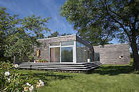 An off-grid house 'Untitled' designed by Langlands & Bell built using a prefabricated building system set in a lawned garden, Kent, UK