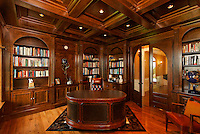 Traditional home office/library with dark paneling and arched doorway.