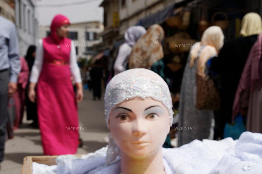 Algerie. Oran. 09 Avril 2011.Des femmes au marche &laquo; Madina Jadida &raquo; (&laquo; la nouvelle ville &raquo;) vetues d'une djelaba et d'un foulard devant un etal de foulards.<br /><br />Women at the market &ldquo;Madina Jadida&rdquo; (&ldquo;the new city&rdquo;) wearing a djellaba and a scarf in front a table full of scarves.