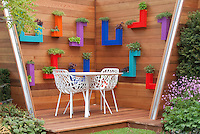 Herbs in hanging container pots in modern bold colors on deck with chairs and table furniture and plantings