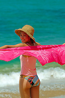 Young woman on the beach with pink sarong blowing in the wind