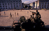 Young people play soccer in a  suburbian area of Rio the Janeiro while Brazil Army search for drugs dealers.
