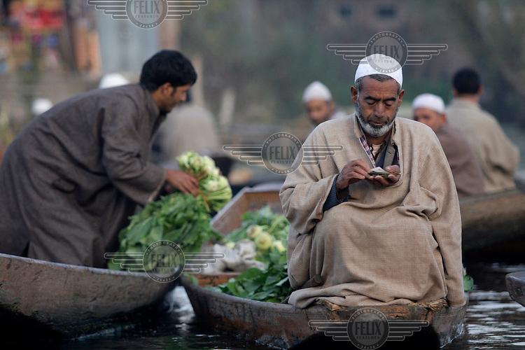 Floating vegetable market. A man counts his money as another unloads vegetables. Srinagar, Kashmir, India. © Fredrik Naumann/Felix Features