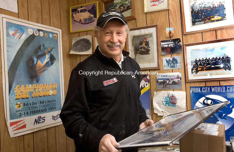 WOLCOTT, CT. 27 January 2010-012710SV01--Frank Briglia of Wolcott stand among his many bobsled photos in auto body shop in Wolcott Wednesday. Briglia is a mechanic for the USA bobsled team.<br /> Steven Valenti Republican-American