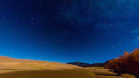 Night scene with stars illuminated by the full moon overhead. The Great Sand Dunes with the Sangre de Cristo Mountains behind, Great Sand Dunes National Park and Preserve, near Mosca, Colorado USA. The park contains the tallest sand dunes in North America, rising about 750 feet above the floor of the San Luis Valley.