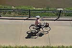 Older woman riding her bike on a sidewalk in Denver, Colorado. .  John offers private photo tours in Denver, Boulder and throughout Colorado. Year-round.