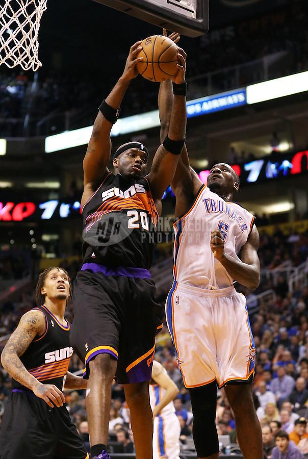 Feb. 10, 2013; Phoenix, AZ, USA: Phoenix Suns center Jermaine O'Neal (left) grabs a rebound against Oklahoma City Thunder center Kendrick Perkins at the US Airways Center. Mandatory Credit: Mark J. Rebilas-