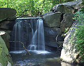 One of the five waterfalls hidden in the Niorth Woods in Central Park, New York. The water falls over a narrow stone bridge into a sun-dappled pond surrounded by enormous rocks in a background of green trees.
