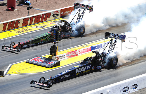 31.03.2012. Las Vegas, USA. Terry McMillen (21 TF) NHRA Top Fuel Dragster and Brandon Bernstein (6 TF) Copart NHRA Top Fuel Dragster heat their tires during the 13th Annual SummitRacing.com Nationals at The Strip at the Las Vegas Motor Speedway in Las Vegas, NV.