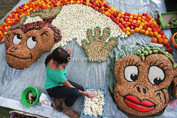 Foto: VidiPhoto..TIEL - Aan de stadsgracht in Tiel wordt donderdag met man en macht gewerkt aan de fruitmozaïeken. Dit jaar maken twintig groepen een afbeelding van aardappels, tomaten en andere groenten en fruit. Er is dit jaar geen vast thema. In totaal wordt er 6000 kilo fruit gebruikt. Vrijdagavond moeten de mozaïeken klaar zijn. De afbeeldingen van fruit en groenten, die 's nachts verlicht worden, blijven liggen tot het fruitcorso van zaterdag 8 september in Tiel..