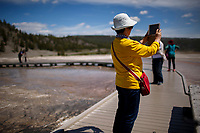 A tourist uses an iPad to photograph the Grand Prismatic Spring in Yellowstone National Park, Wyoming on Tuesday, May 23, 2017. (Photo by James Brosher)