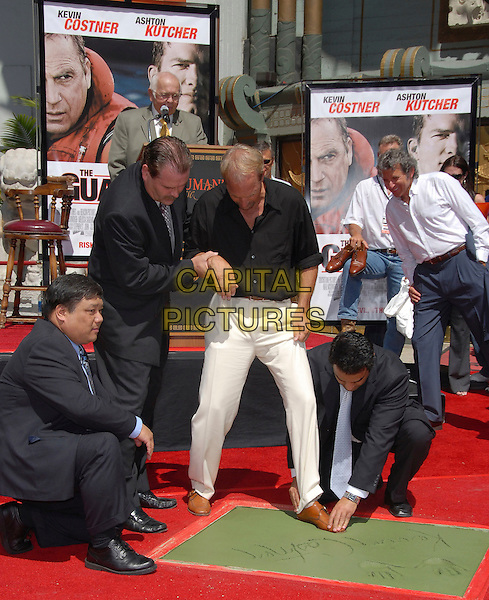 KEVIN COSTNER.At The Kevin Costner Hand & Footprint Ceremony held at The Grauman's Chinese Theatre in Hollywood, California, USA..September 6th,2006 .Ref: DVS.full length black shirt white trousers holding hand.www.capitalpictures.com.sales@capitalpictures.com.©Debbie VanStory/Capital Pictures