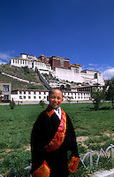 Potala Palace on mountain with child boy welcoming tourists at the home of the Dalai Lama  in capital city of Lhasa Tibet China