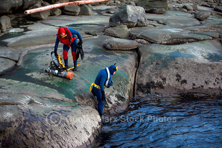 Scuba Divers with Oxygen Tanks / Diving Cylinders prepare for diving in Pacific Ocean, along the West Coast near Vancouver, BC, British Columbia, Canada