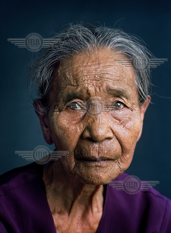 """Mastia (born 1927) was one of tens of thousands of 'comfort women' forced into prostitution by the Japanese military during World War II..Mastia was taken from home by soldiers along with 15 other girls and transported to barracks in Cimahi. While the others were forced into prostitution, a Japanese captain picked her from the group and commandeered her as his private comfort woman. For half a year, she lived as a forced concubine in his quarters, an Indonesian military aid standing guard at her door. When the captain was reassigned, she had to accompany him. This way she stayed in several barracks until the end of the war. After returning home, she went through a religious cleansing ceremony to wash away the 'sin'. """"People nevertheless continued to call me a 'Japanese hand-me-down'. That made me very sad. I still think about it often."""" She has been married four times. """"I was very much in love, but after a few years the marriages often failed because we didn't like each other all that much anymore. With the last man I was married 25 years, but he took on another woman because I couldn't have any children."""" Since her husband's death she lives by herself and still works in the rice fields.."""